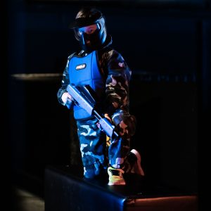 a boy in blue playing paintball in indoor paintball ljubljana